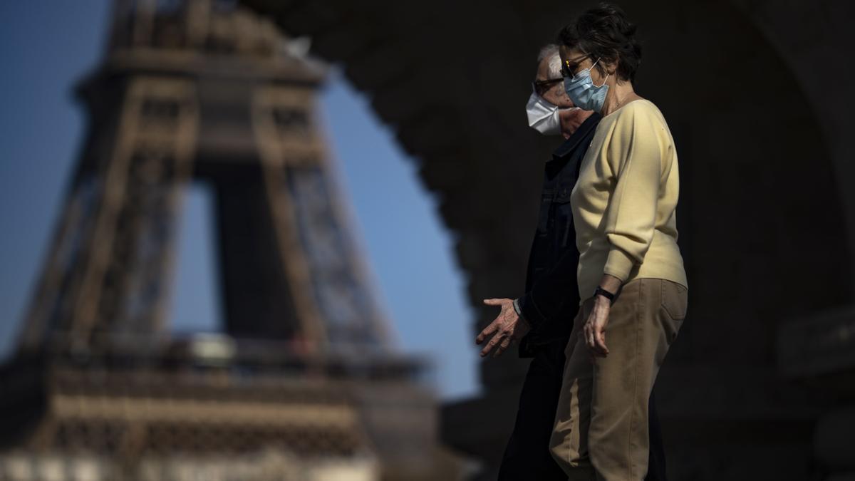 Dos personas caminan frente a la Torre Eiffel con Francia en plena desescalada