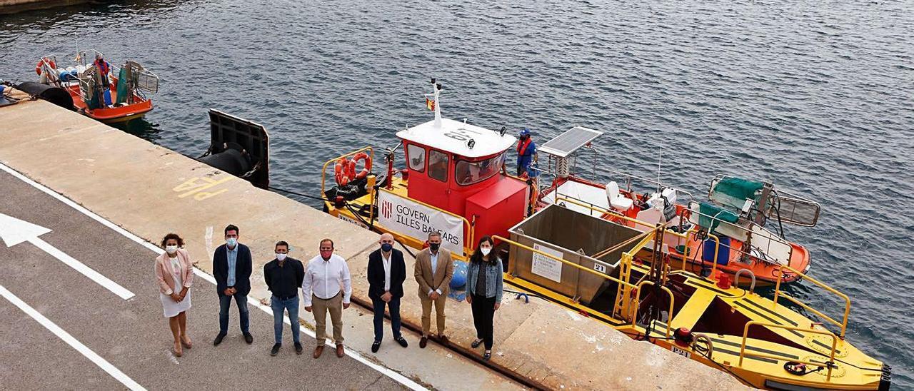 Miquel Mir, en el centro, junto a la embarcación Pelícano, ayer, en el puerto de Sant Antoni. | J. A. RIERA