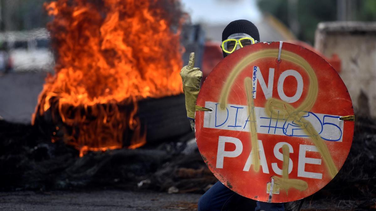 Un manifestante sostiene un cartel durante una protesta en Cali, epicentro de las movilizaciones.