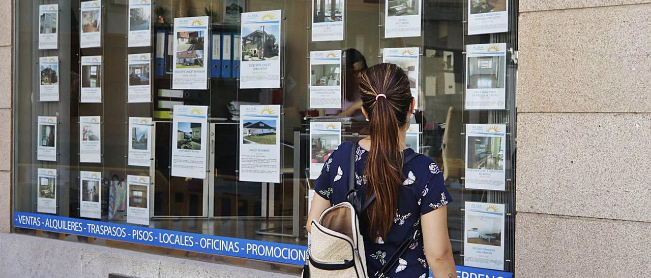 Una joven observa los anuncios del escaparate de una inmobiliaria en Vigo.     // ALBA VILLAR