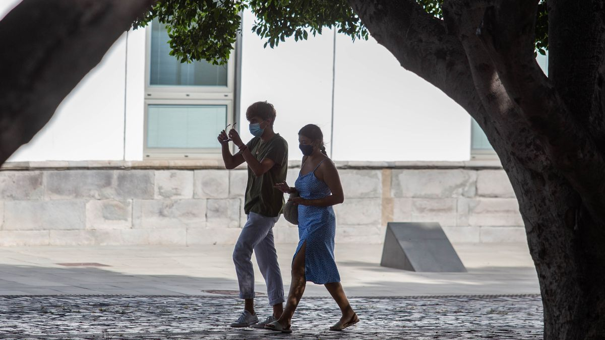 Una pareja con mascarilla pasea por el centro de la ciudad de Santa Cruz.