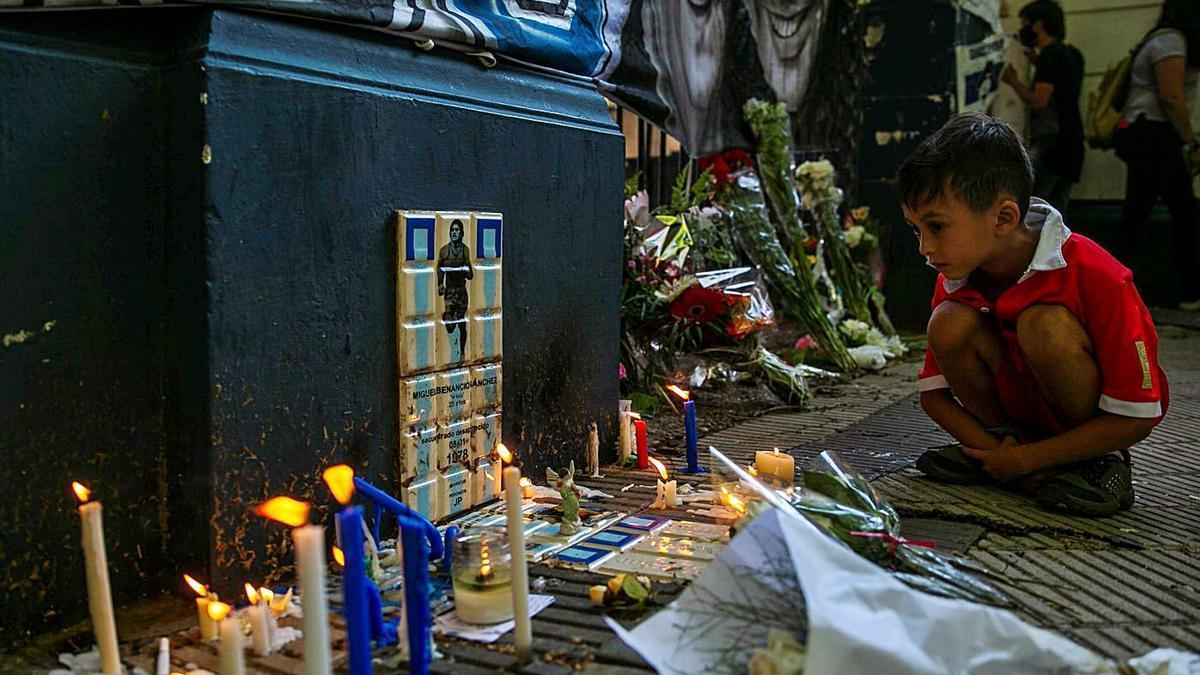 Un niño observa un altar improvisado en honor a Maradona en La Plata.