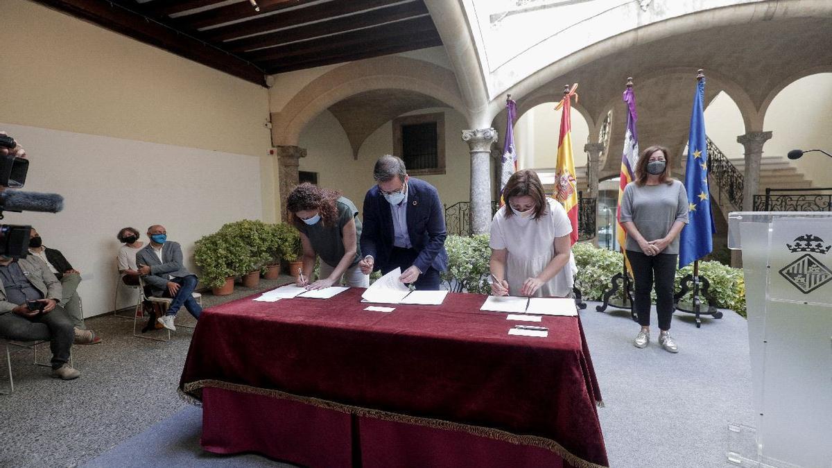 El alcalde, José Hila, la presidenta del Consell de Mallorca, Catalina Cladera y la consellera de Presidencia, Mercedes Garrido, firman el convenio con la supervisión de la presidenta del Govern, Francina Armengol.