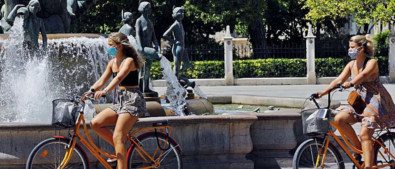 Dos turistas cruzan ante la fuente de la plaza de la Virgen.   M.A.MONTESINOS