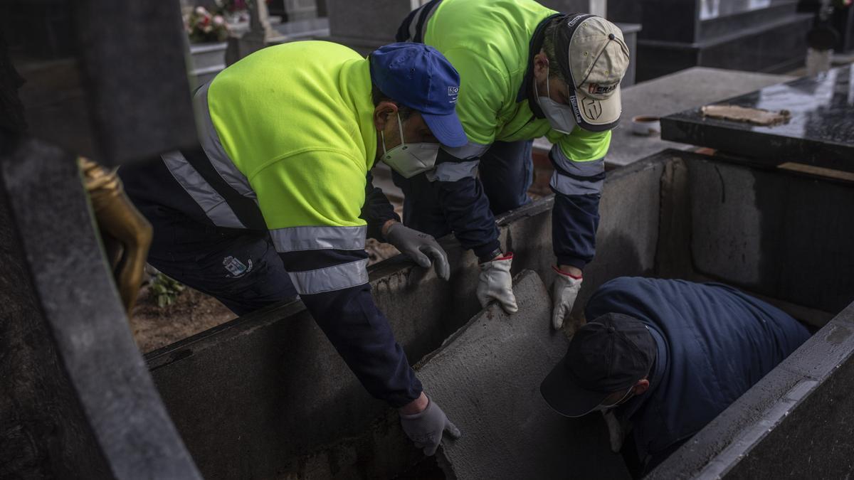 Los operarios preparan una tumba para un enterramiento en plena pandemia