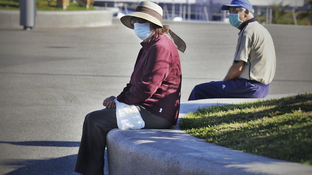 Dos personas mayores descansan manteniendo la distancia de seguridad y con sus mascarillas en Santa Cruz.