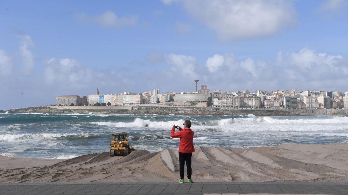 Una persona toma una imagen en la playa coruñesa de Riazor.