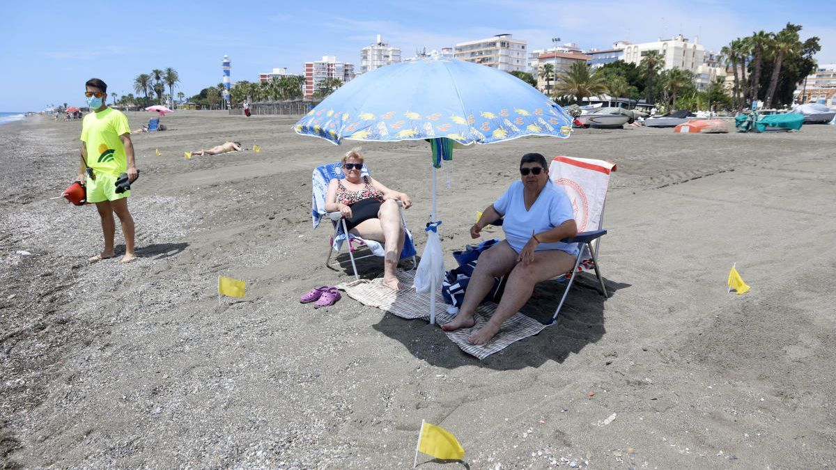 Dos bañistas disfrutan del primer día de playa en su parcela de arena, en Vélez-Málaga.