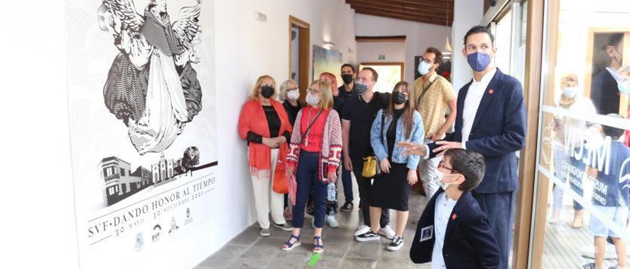 Una de las galerías del Museo Etnográfico con el gran cartel que simboliza la nueva muestra inaugurada con motivo de los  aniversarios de la imagen y la parroquia.