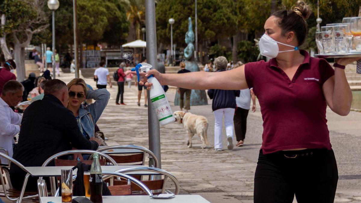 Una camarera pulveriza con desinfectante una mesa en una terraza de Mallorca.