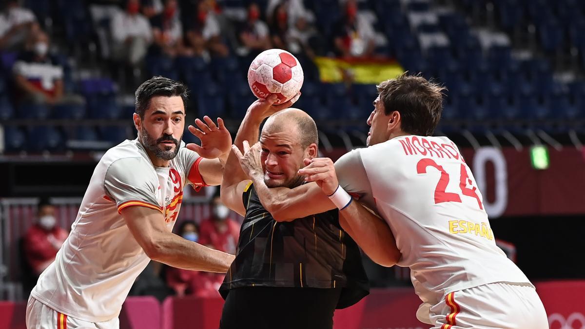 Raúl Entrerríos y Viran Morros intentan frenar a Paul Drux en el Alemania-España de los Juegos Olímpicos de Tokio