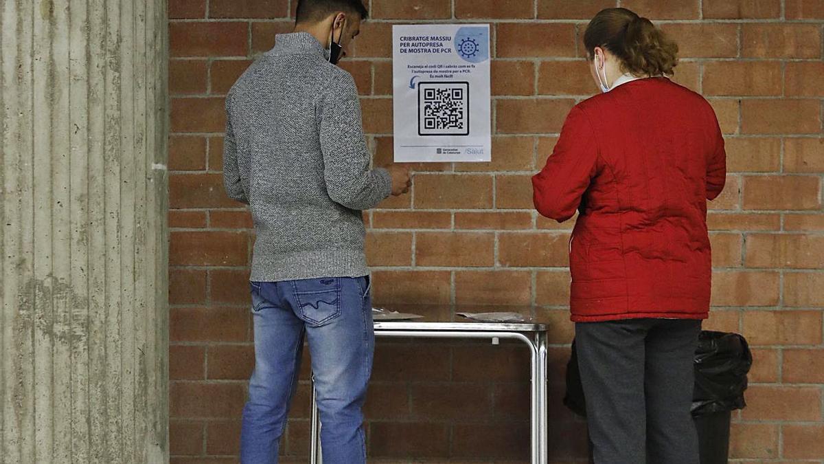 Dos joves agafant una mostra per al cribratge de Girona, el mes passat. | ANIOL RESCLOSA