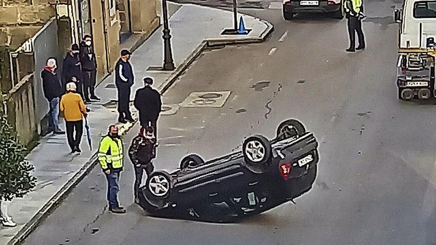 Ilesa tras colisionar su coche con otro aparcado y volcar en la vía sobre su techo