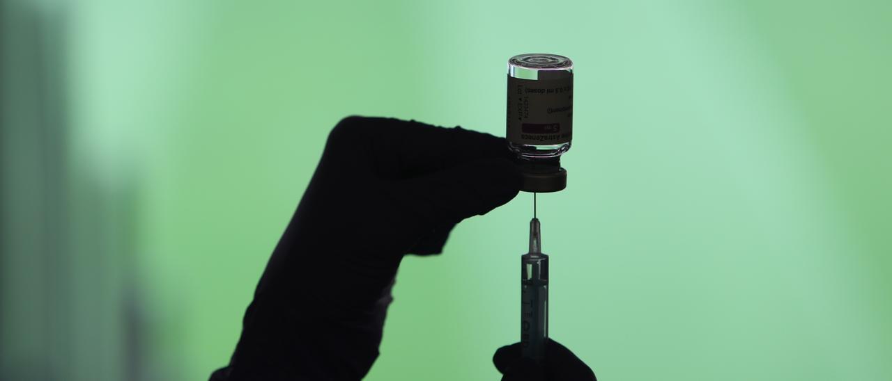 Un profesional sanitaria sostiene una jeringuilla y un vial con la vacuna del Covid-19.