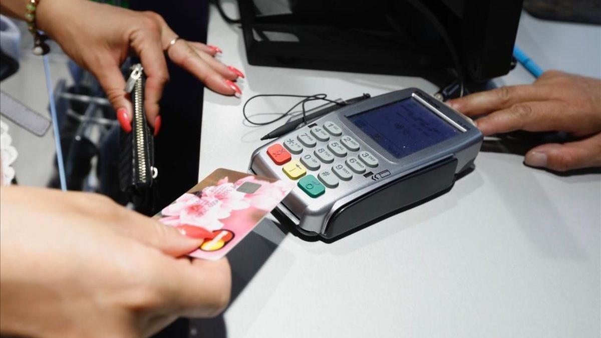 Cliente realizando un pago con un tarjeta en un comercio.