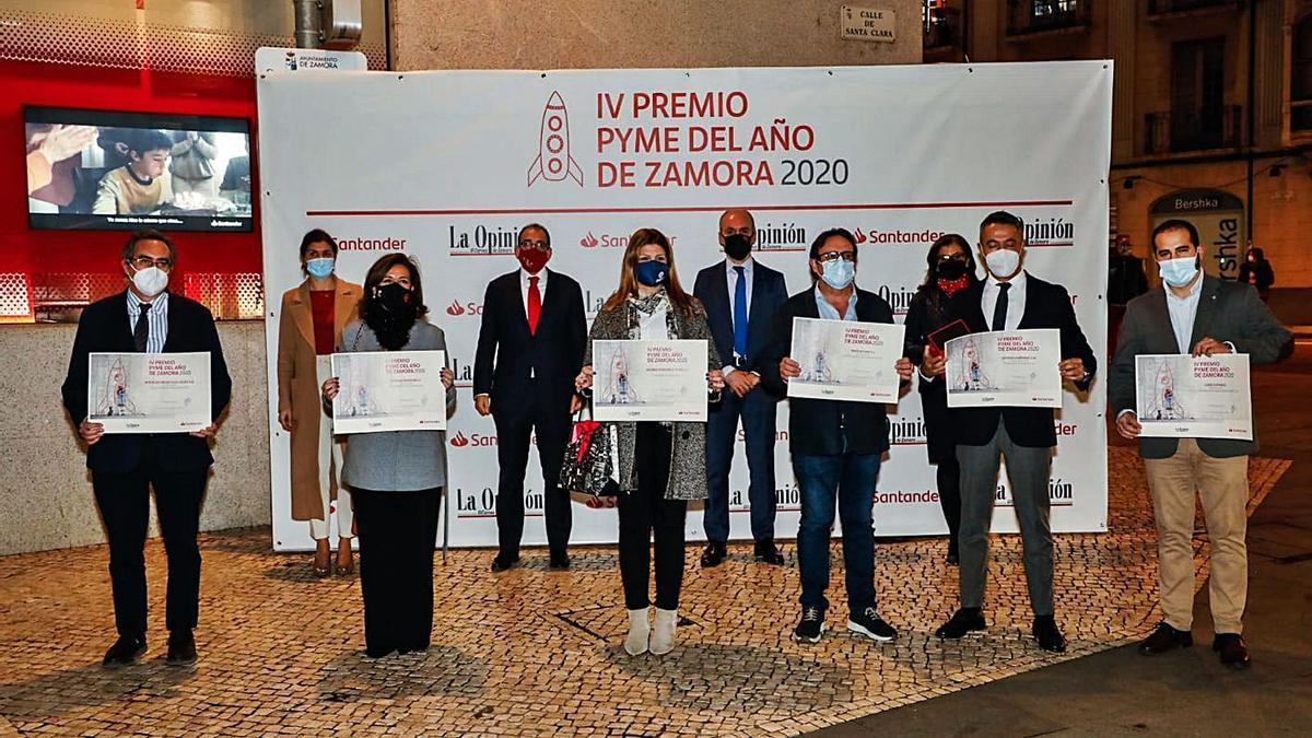 Foto de familia de los premiados, a la entrada de la oficina del Banco Santander.   Nico Rodríguez