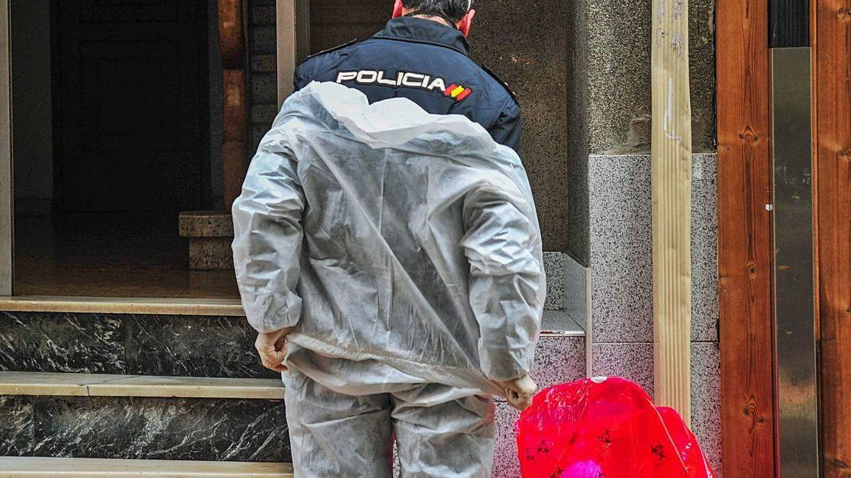 Un policía nacional en Vilagarcía, durante su trabajo, enfundando un traje EPI.