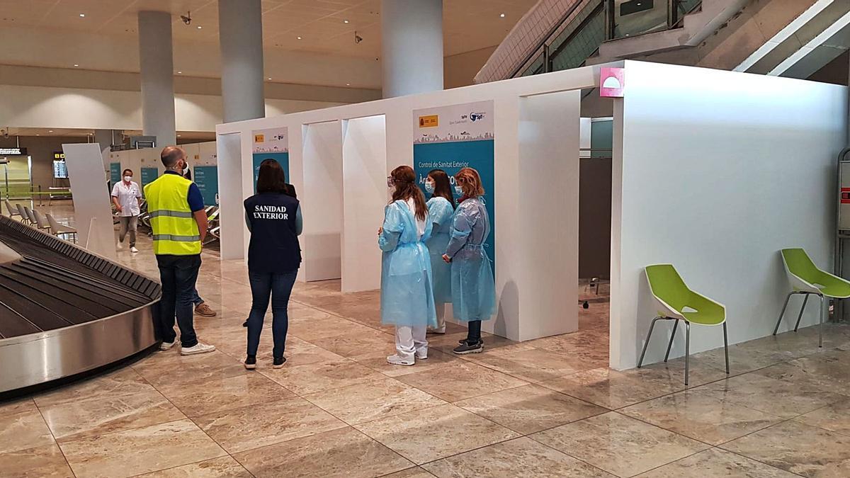Personal de Sanidad Exterior y Quirón Salud esperando ayer a los pasajeros en las dependencias habilitadas en la zona de llegadas, para realizar tests de antígenos.