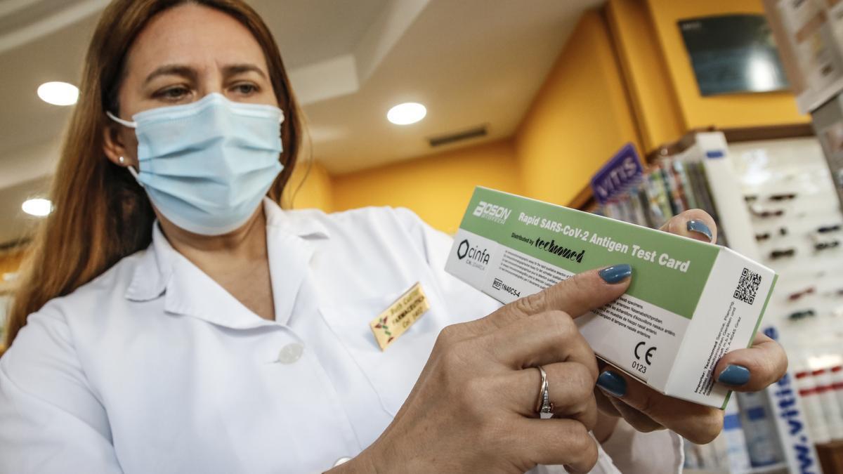 La farmacéutica Ruth Cuéllar muestra dos test de antígenos en la Farmacia Claros, en Cáceres.
