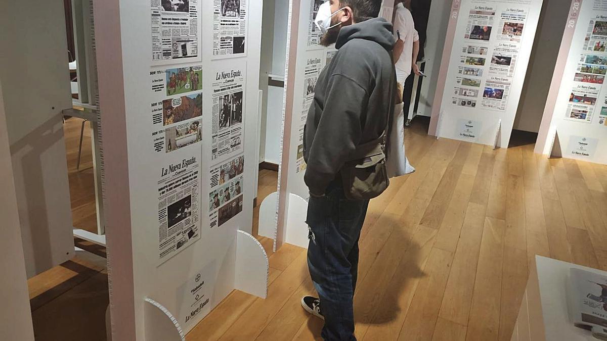 Sobre estas líneas, Fabián Díez observa uno de los paneles de la exposición. En el círculo, Higinio García señala una viñeta sobre esquí. | A. Velasco