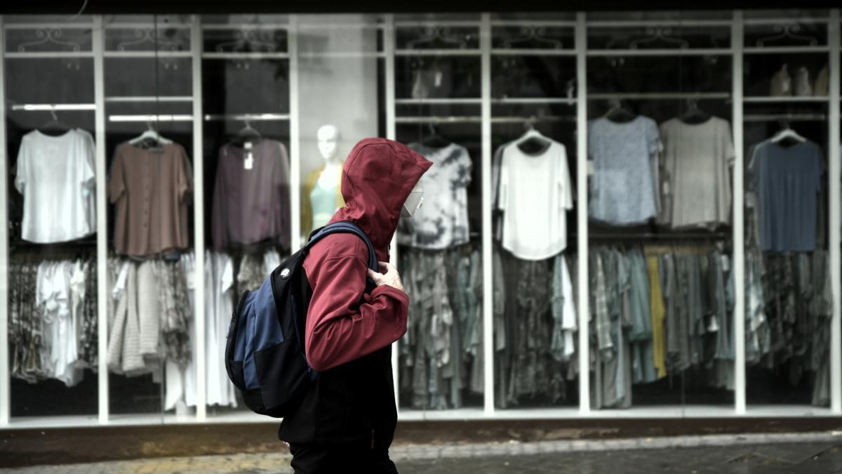 Un hombre pasea frente a una tienda.