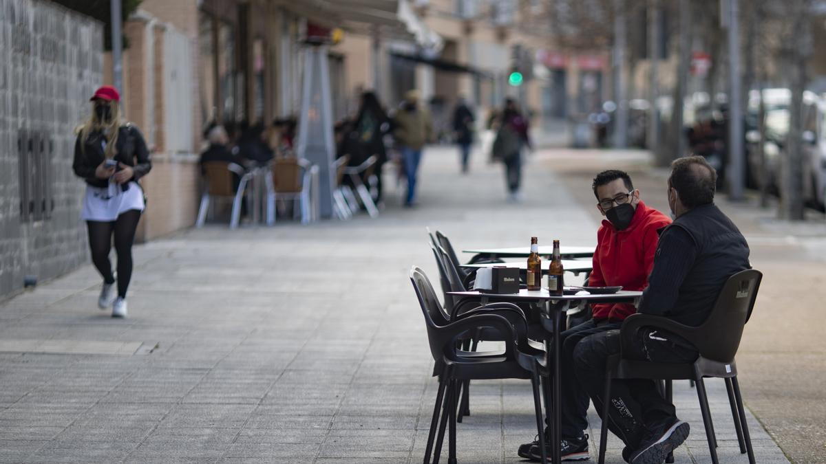 Dos hombres toman algo en una terraza en Madrid.