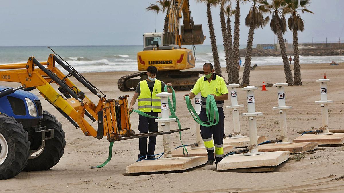 Los operarios instalan las duchas en la arena de la playa de Canet d'En Berenguer para que todo esté listo para la operación verano. | DANIEL TORTAJADA