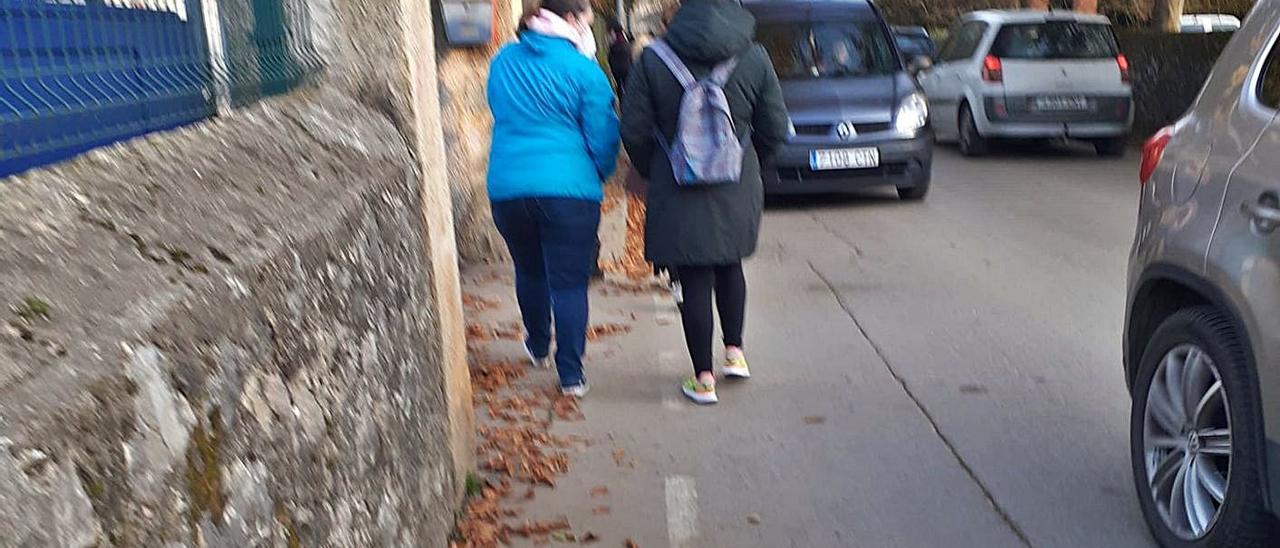 Dos estudiantes, caminando entre coches para acceder al centro escolar de Posada de Llanes. | E. S. R.