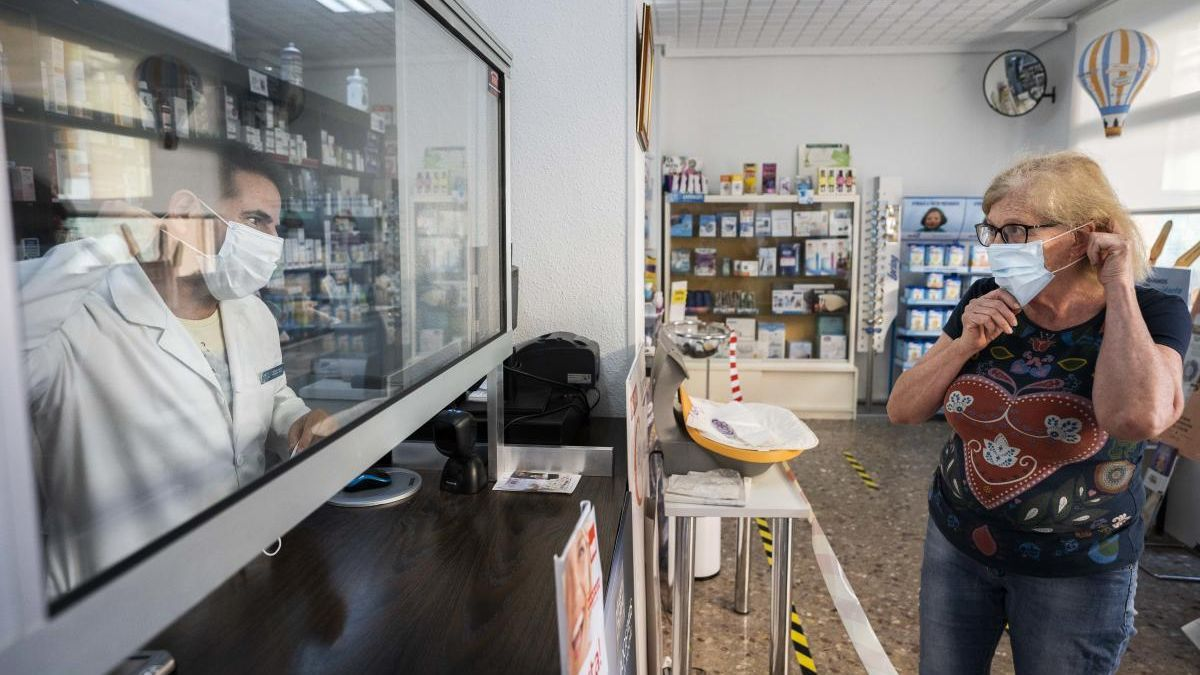 Una mujer compra mascarillas en una farmacia.
