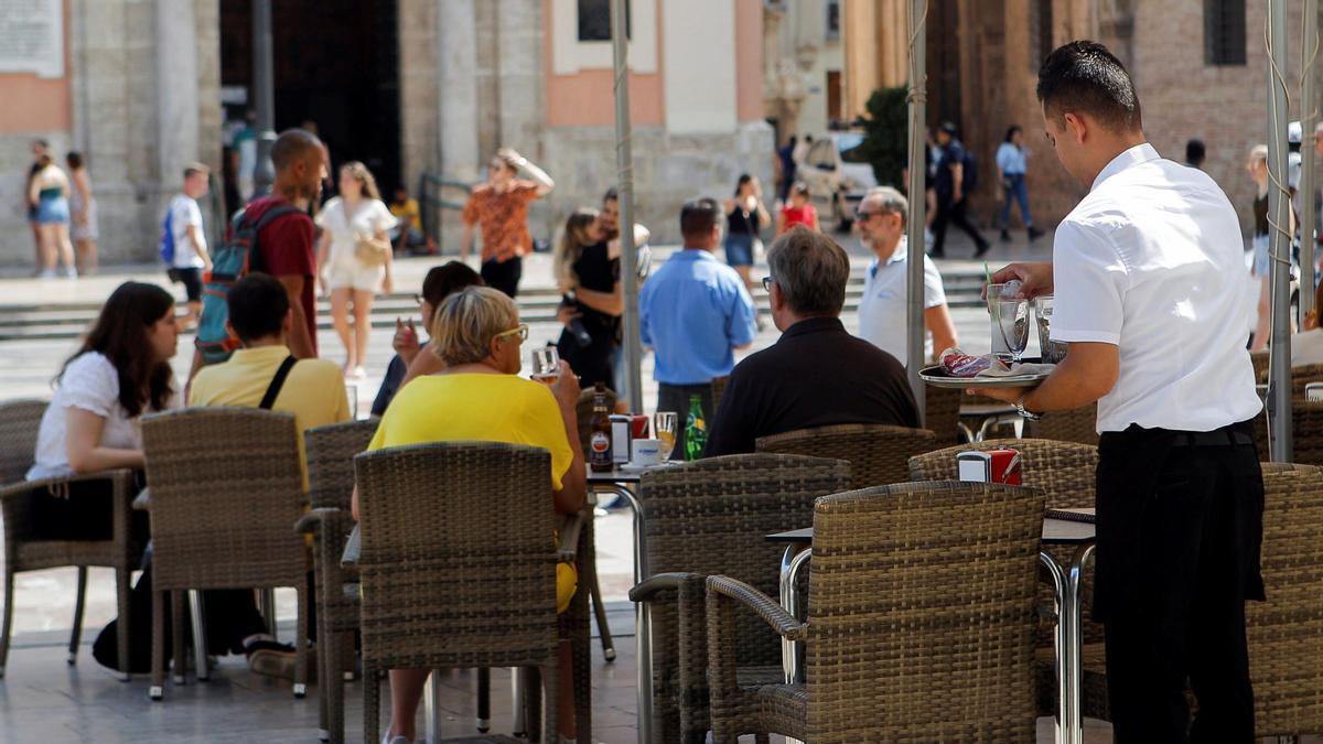 Un camarero atiende una terraza.