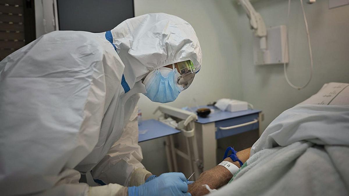 Una sanitaria atiende a un paciente en la planta covid del Hospital General.  | LEVANTE-EMV