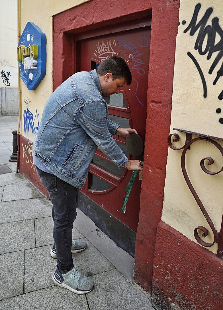 Pepe Reina, cerrando la puerta de su local de ocio nocturno  de la calle Canóniga de Oviedo.
