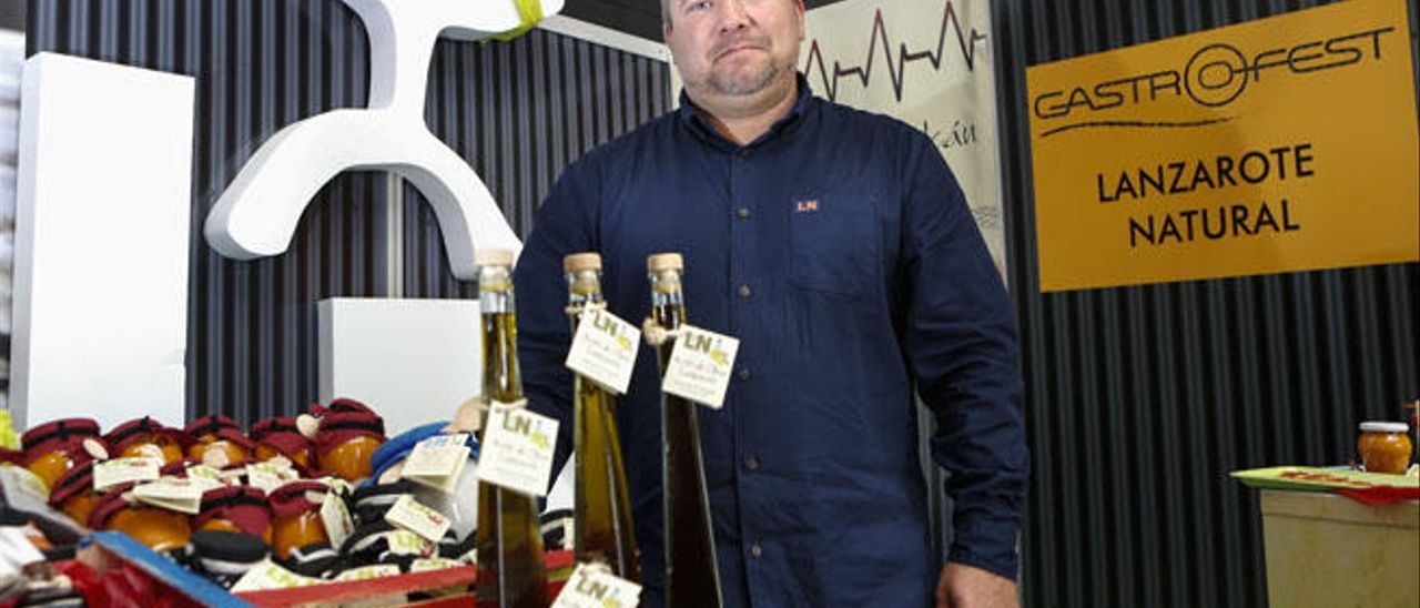 Daniel Lasso, propietario de Lanzarote Natural, con tres botellas de aceite de Lanzarote en primer término.