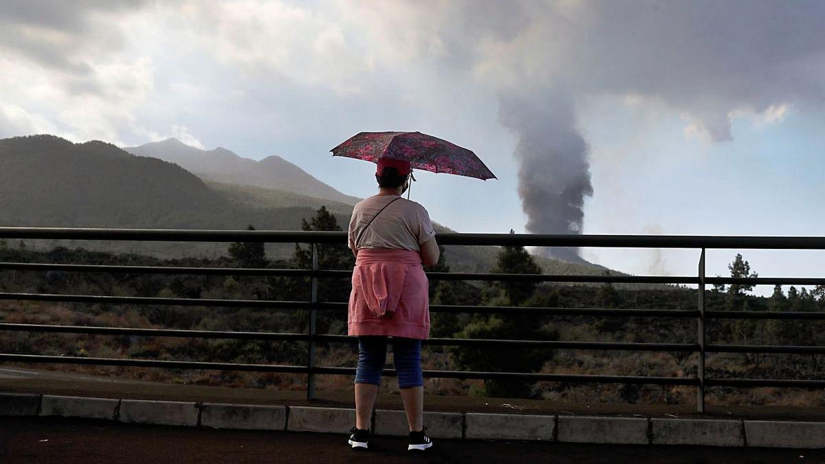 Una mujer contempla desde la distancia el volcán de La Palma humeante.