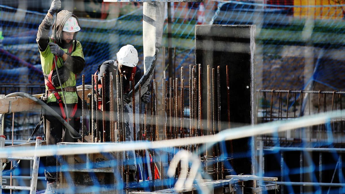 Dos operarios trabajan en una obra en construcción.