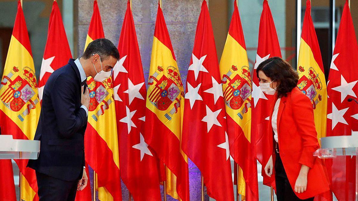 Sánchez y Ayuso, saludándose durante su comparecencia conjunta tras la reunión.