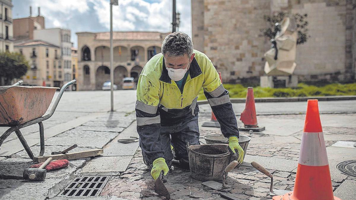 Un trabajador de la construcción arregla desperfectos en el pavimento de la Plaza Mayor de Zamora.