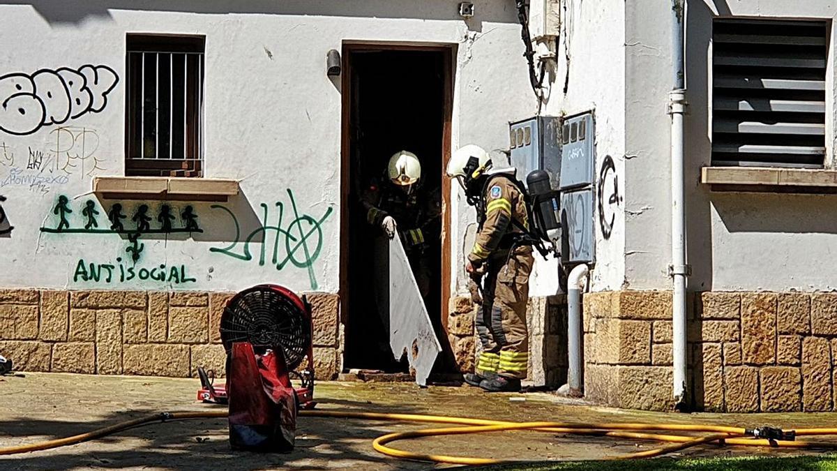 Los bomberos retiran el material dañado de los vestuarios donde se originaron las llamas.  |  LNE