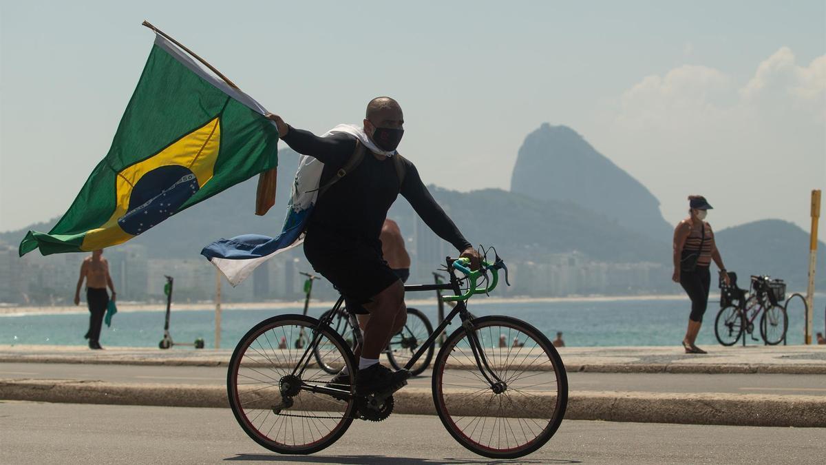 Un hombre con una bandera de Brasil durante protestas contra restricciones en Río de Janeiro.