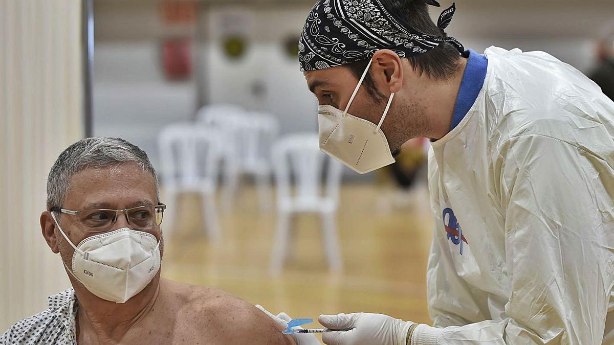 Un enfermero del 061 administra una vacuna en el pabellón Cabezo Beaza de Cartagena. | IVÁN URQUÍZAR