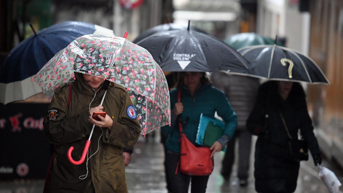 Gente protegiéndose de la lluvia con paraguas.