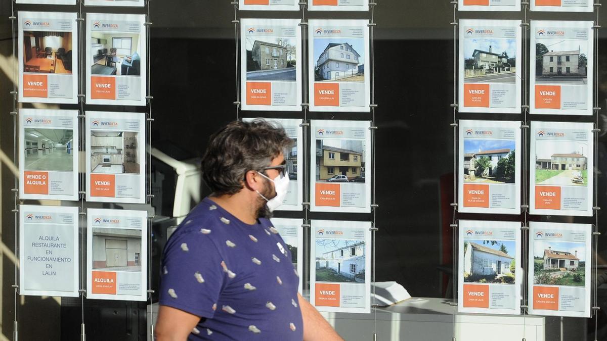 Un hombre pasa junto a una inmobiliaria.