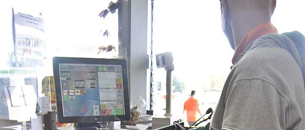 Un empleado de la gasolinera asaltada en La Fresneda, ayer, abriendo la caja registradora vacía.   Andrés Illescas