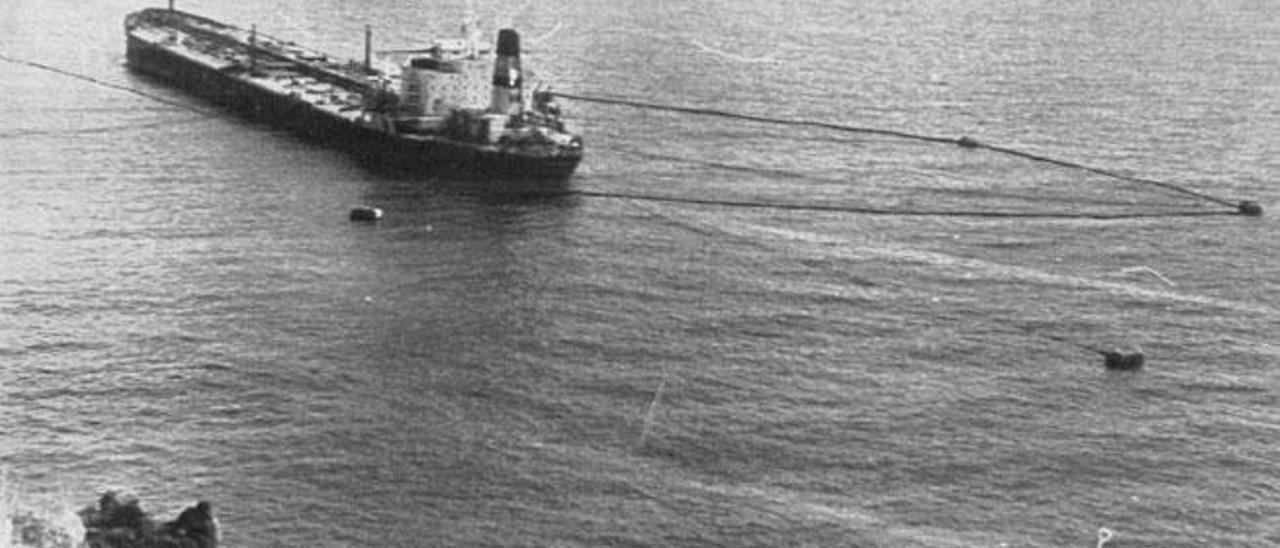 El petrolero 'Aragón', rodeado por un cordón anticontaminante, fondeado frente al muelle de La Hondura en enero de 1990.