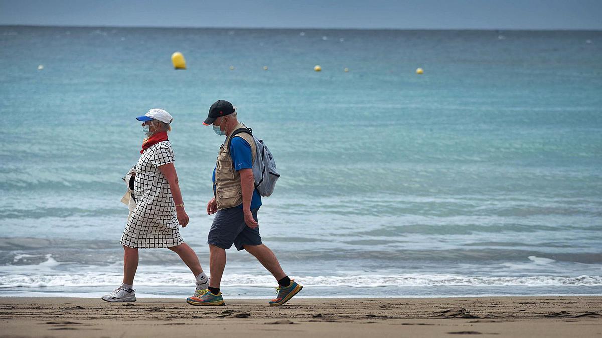 Dos turistas caminan por la orilla en la playa de Las Vistas, en Arona.