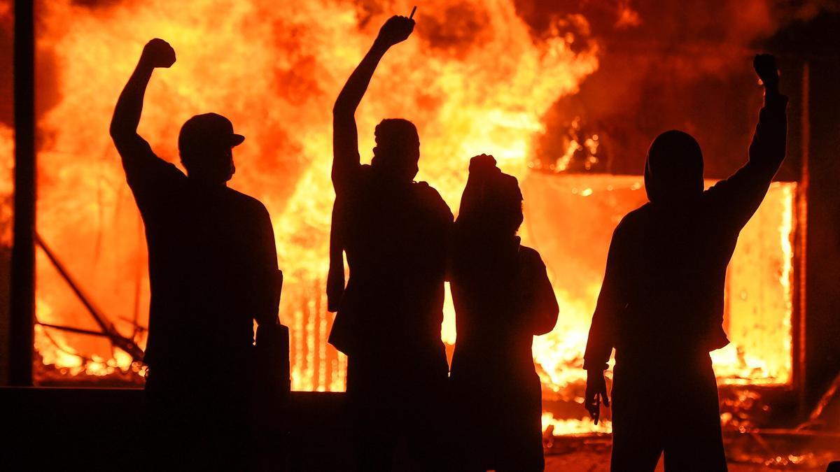 Manifestantes alzan el puño frente a una tienda en llamas en Mineápolis. |