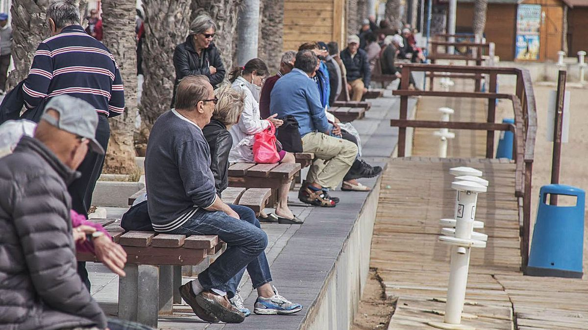 Seniors on the benches of Torrevieja's Cura beach promenade in a file image.