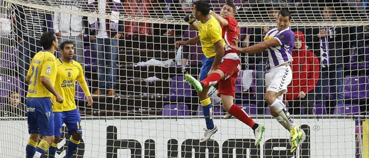 El portero amarillo Raúl Lizoain despeja con los puños un centro colgado del Valladolid con la oposición del lateral diestro David Simón.