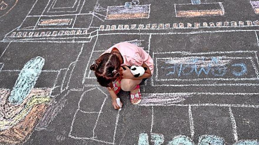 Una niña de corta edad juega con una tiza en la calle.