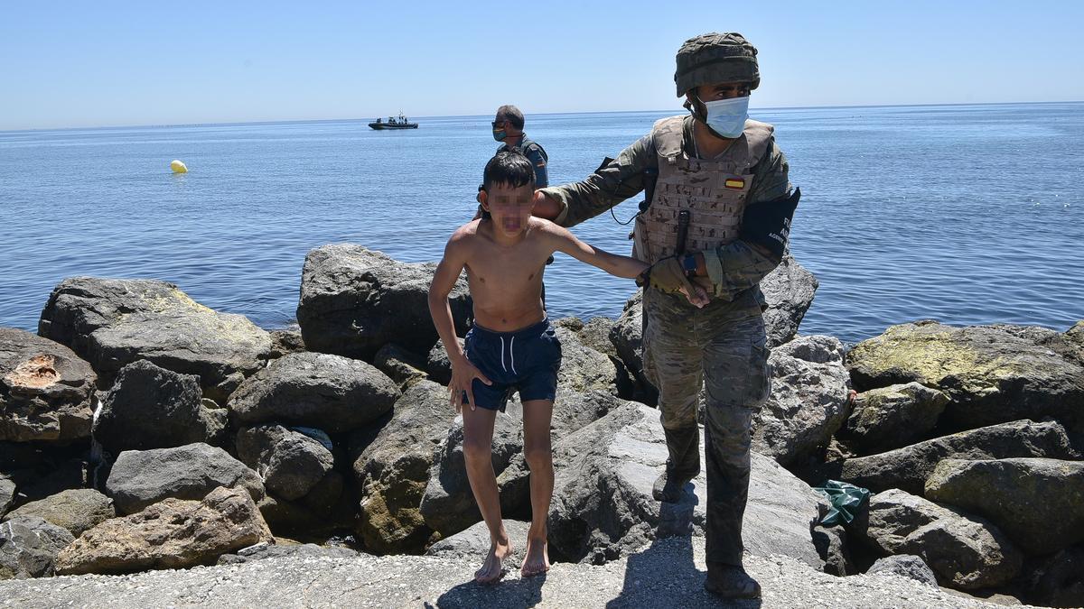 Un militar español ayuda a un niño Marroquí tras llegar a nado a Ceuta.